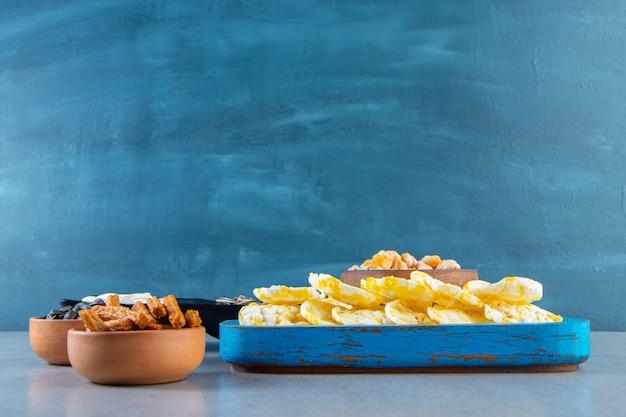 Vari snack in ciotole, sullo sfondo di marmo.