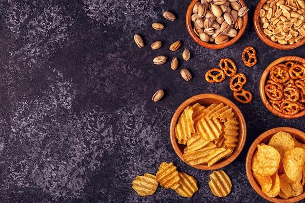 Различные закуски в мисках с картофельными чипсами, орехами и кренделями
