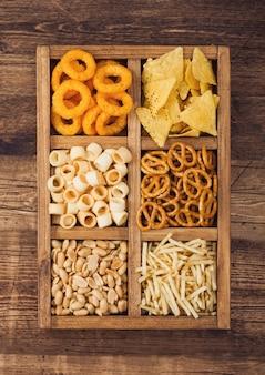 木製の背景にヴィンテージ木製ボックスの様々なスナック。オニオンリング、ナチョス、塩味のピーナッツとポテトスティックとプレッツェル。ビールや炭酸飲料に適しています。