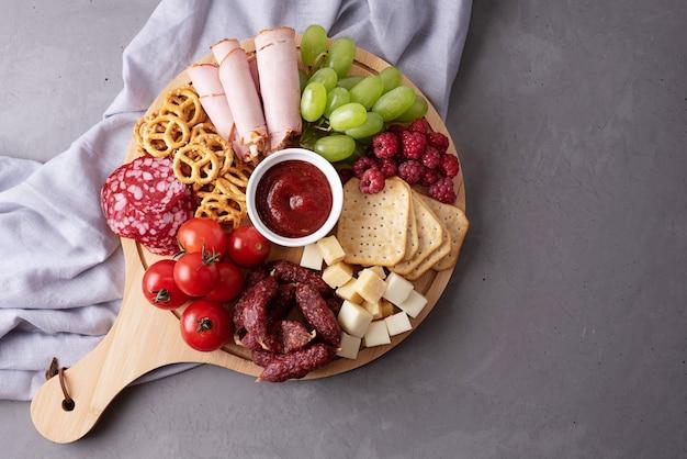 灰色の背景の丸い豚肉ボード上のさまざまな軽食、前菜のパーティー、クローズアップ。