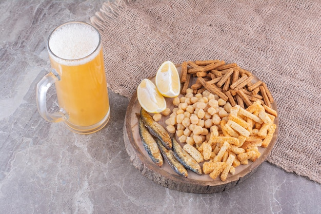Various snacks on wooden piece with glass of beer. high quality photo