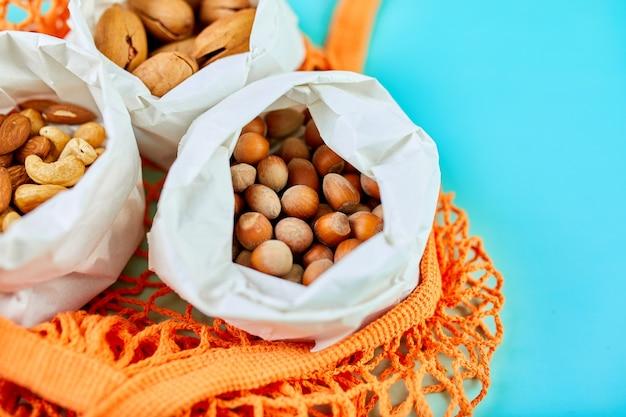 Различные виды орехов на столе в пакетах в сумке для покупок на синей поверхности