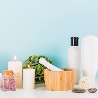 Various spa products with illuminated; candles; mortar and pestle on white tabletop