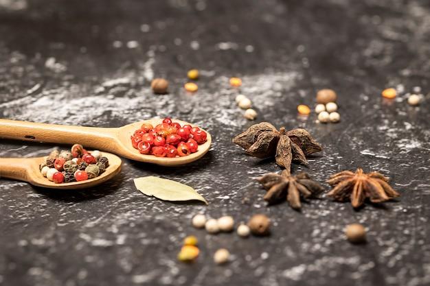 黒い石のテーブルの上に木のスプーンでさまざまなスパイスミックス。