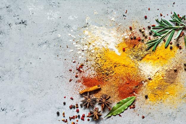 さまざまなスパイスパウダーパプリカカレーコリアンダージンジャードライオニオンとガーリックターメリックシナモンペッパーアニスとハーブローズマリー月桂樹の葉、灰色の背景インド料理とアジア料理