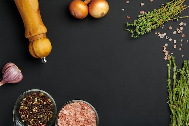 黒板に様々なスパイスと調味料。食品の領収書、メニュー、または食品ブログのコンセプトのボードモックアップ。上面図