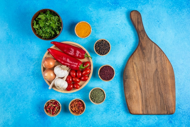 Various spices around wooden board with plate of vegetables.