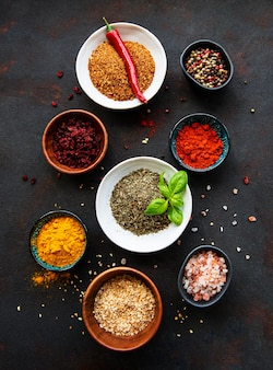 Various spices in a bowls on black concrete background