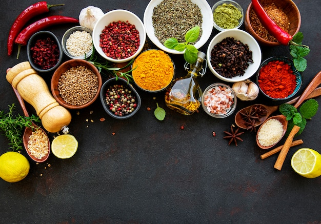 Various spices in a bowls on black concrete surface. top view copy space.