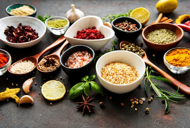 Various spices in a bowls on black concrete table. top view copy space.