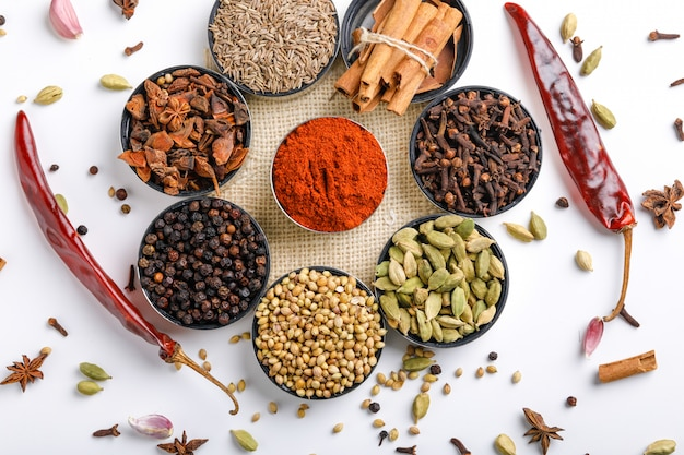 Various spices in a bowls on white