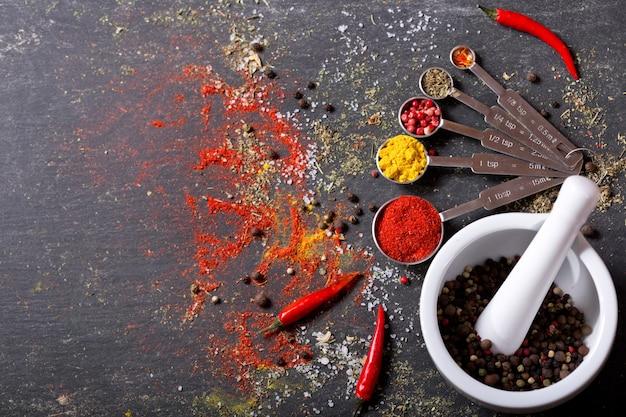 Различные специи для приготовления на темном столе, вид сверху