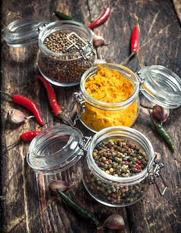 Various spices in glass jars. on a wooden background.