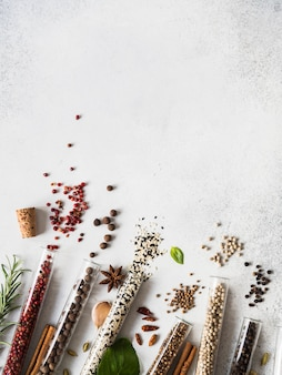 Various spices in glass test tubes and fresh herbs on gray background. set of various spices and herbs flat lay. copy space