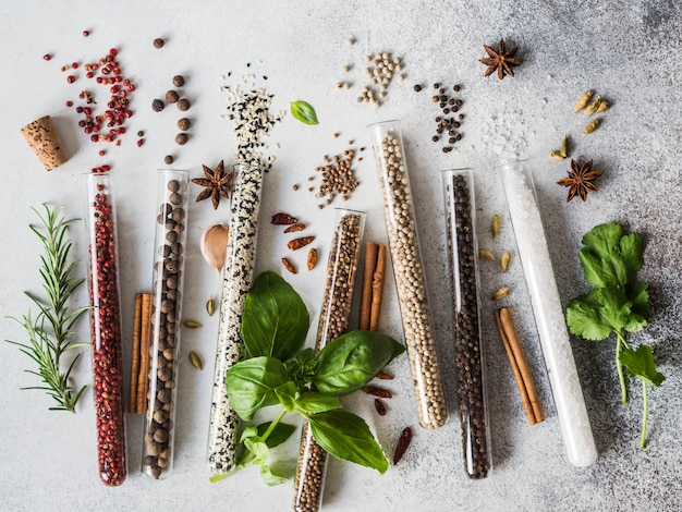 Various spices in glass test tubes and fresh herbs on gray background. set of various spices and herbs flat lay