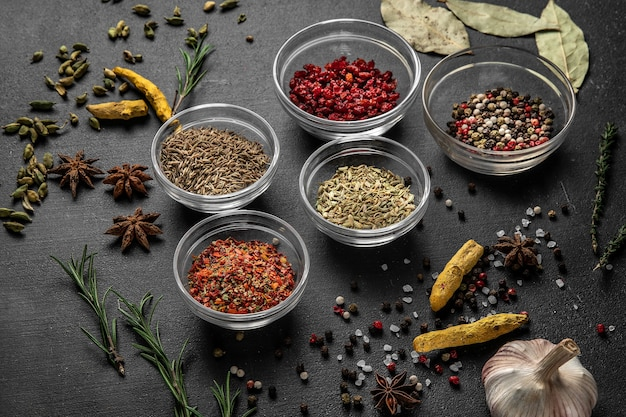 Various spices on a gray surface. seasoning in glass cups side view