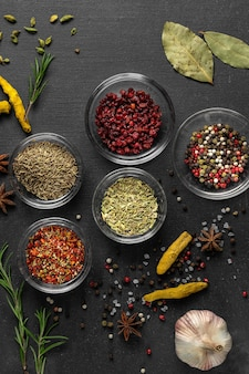 Various spices on a gray surface. seasoning in glass cups top view, close-up, vertical photo