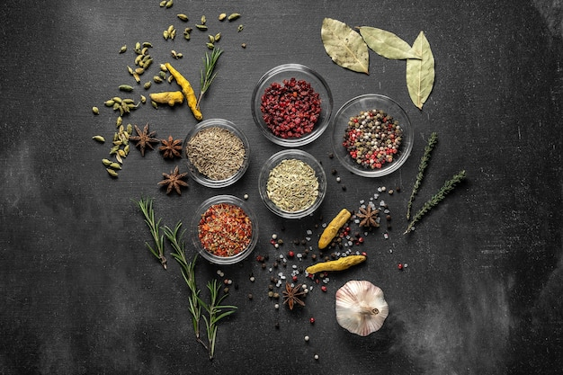 Various spices on a gray surface. seasoning in glass cups top view