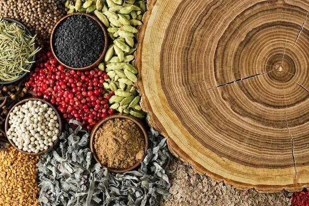 Various spices and herbs background. condiments with empty woode
