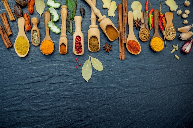 Various of spices and herbs in wooden spoons on the black stone.