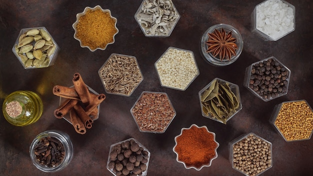 Various spices in hexagonal jars appear on a metal rusty baking sheet