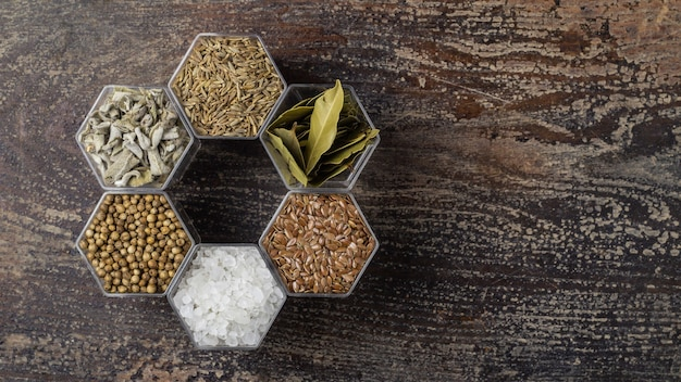 Various spices in hexagonal jars on a wooden surface