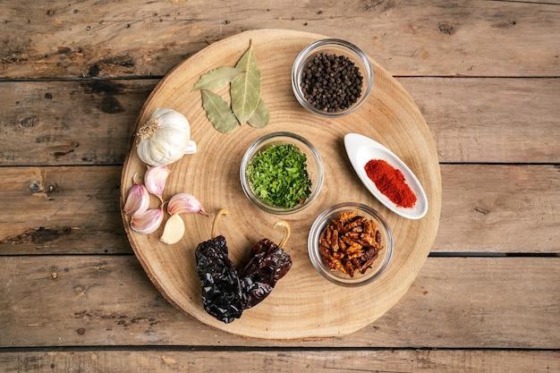 Различные специи в стеклянной миске на деревянном столе