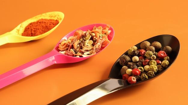 茶色の背景にプラスチックスプーンでさまざまなスパイス。スペースをコピーします。ピーマン、赤燻製パプリカ、12種類の野菜の調味料の混合物。