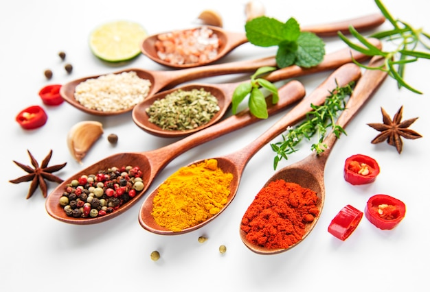 Various spices isolated on white surface, top view