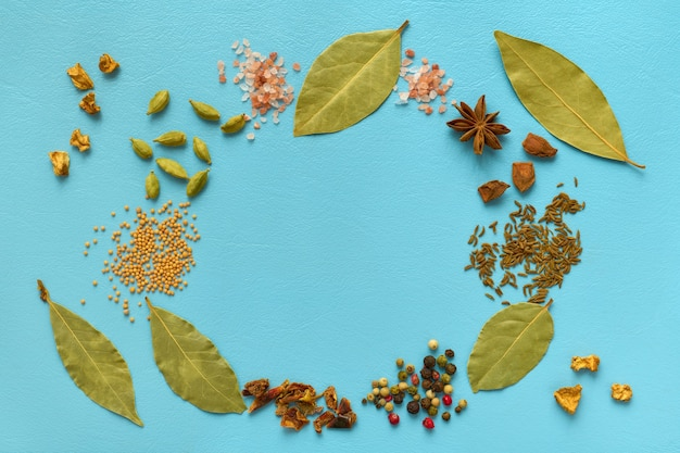 Various spices laid out on blue with round copy space