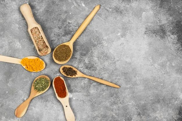 灰色の背景にさまざまなスパイス。トップビュー、コピースペース。食品の背景