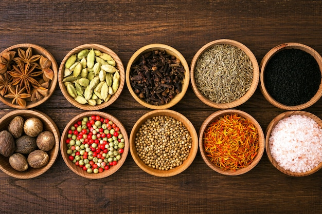 Various spices and seasonings in bowls on wood