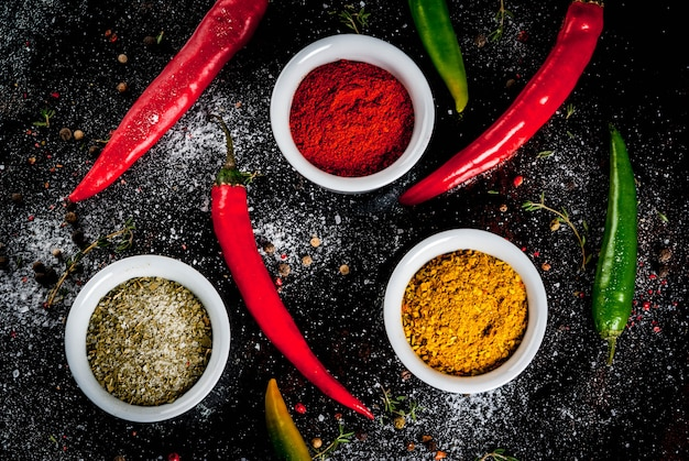 Various spices and seasonings. cooking .  turmeric, curry, paprika, pepper, chili, dried basil, salt, fresh chili, thyme. black rusty metal . top view, .