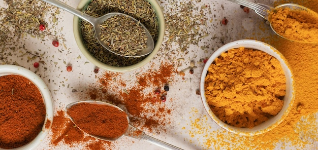 Various spices and seasonings: turmeric, paprika and provencal herbs on light brown stone table. cooking table and copy space for text, top view