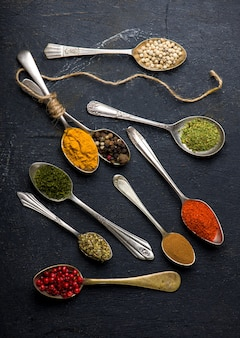 Various spices spoons on black table. top view with copy space