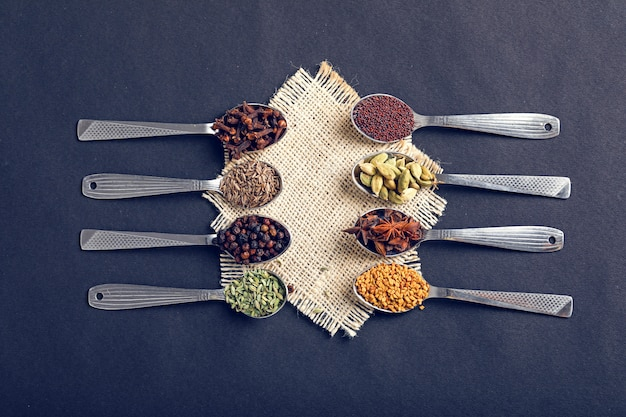 Various spices in spoons on dark background
