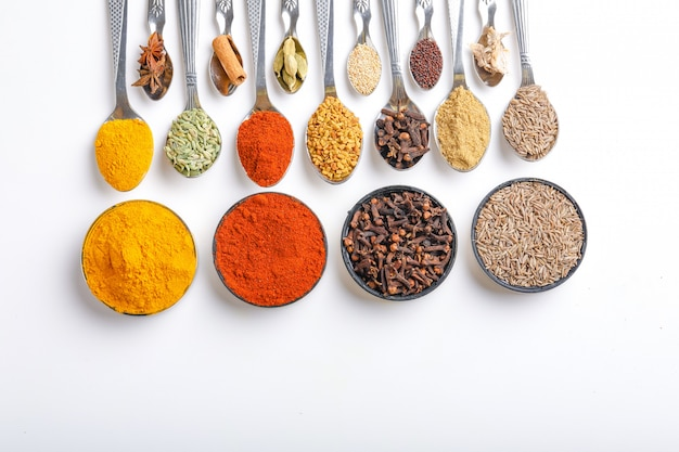 Various spices in spoons on white background