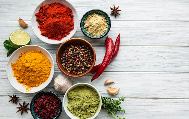 Various spices  on white wooden surface top view