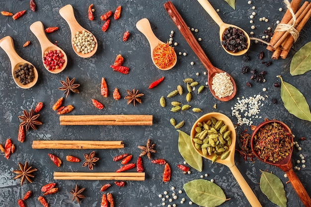 Various spices in wooden spoons on dark stone table