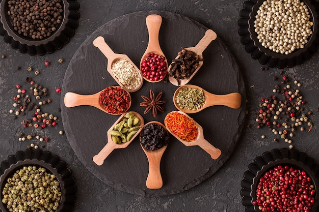 Various spices in wooden spoons on dark stone table.