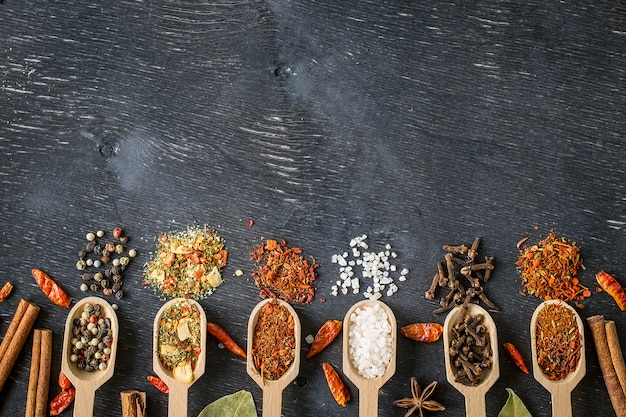 Various spices in wooden spoons  on dark wooden table background
