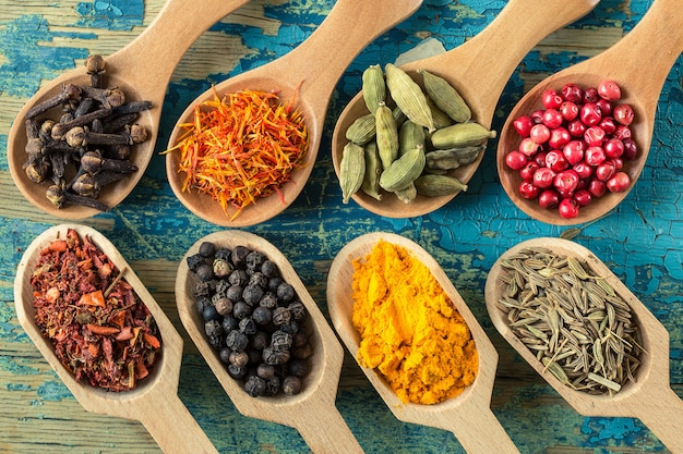 Various spices in wooden spoons on wooden