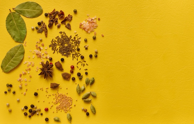 Various spices on yellow background. top view copy space
