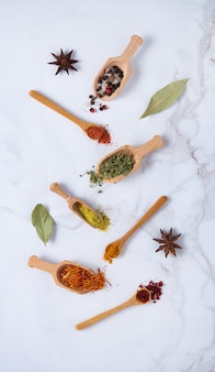 Various spoons of oriental spices on marble background