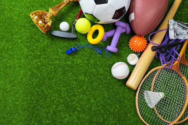 Various sport tools and balls on grass, top view background