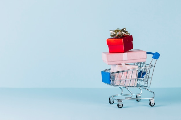 Various stacked gift boxes in shopping cart on blue background