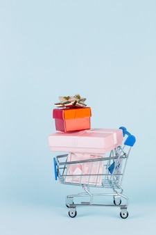 Various stacked parcels in shopping cart on blue backdrop
