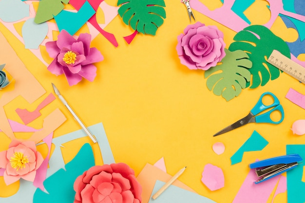 Various stationary supplies, colored paper, paper craft flowers on yellow table