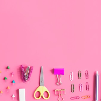 Various stationeries at the bottom of pink background