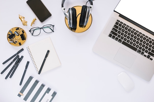 Various stationeries near laptop and headphone on white background